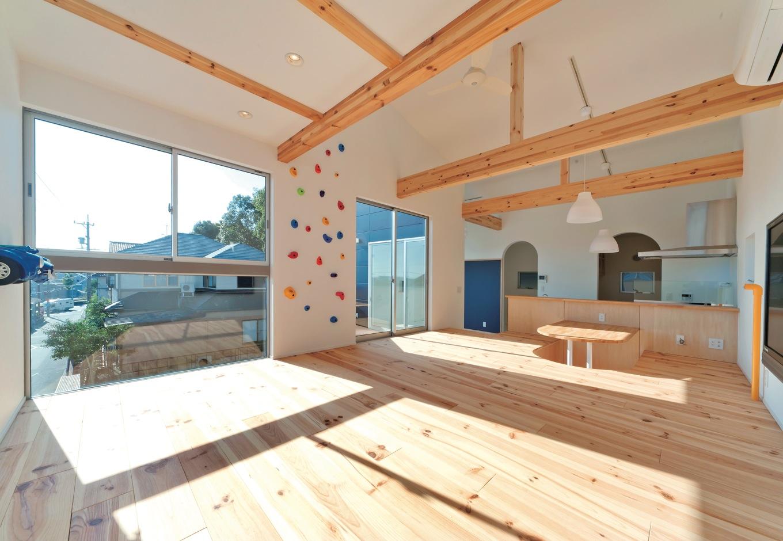 MABUCHI【デザイン住宅、収納力、ガレージ】パイン材の風合いが心地よいシンプルなLDK。リビングは小上がりにして、部屋中をゴロゴロで きるようにした。対面キッチンの向かいには掘り座卓を配置