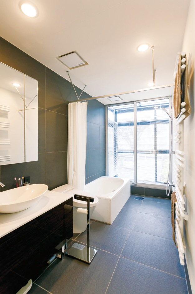 MABUCHI【デザイン住宅、建築家、鉄骨鉄筋コンクリート構造】ホテルライクなサニタリー。タオルを乾かすためのホットハンガーも装備。奥が洗濯物を干すサンルームになっている