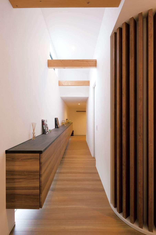 MABUCHI【デザイン住宅、建築家、ガレージ】玄関からリビングへつながる廊下。宙に浮かぶように長い収納棚を造作し、地窓から光を取り入れて十分な明るさを確保。コーナーの木の格子はご主人が完成見学会で一目惚れして採用した