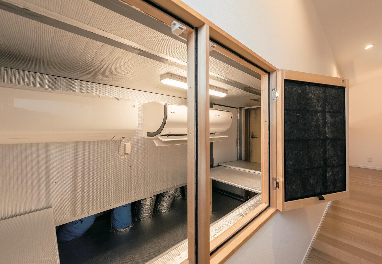 これが全館空調システムの肝となる2階階段ホールの空調室。可動しているのは通常の家庭用14畳のエアコン1台(も う一台は予備)。これだけで子世帯すべての空間の空調が可能となっている