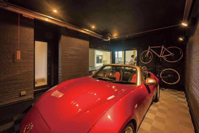 イデキョウホーム【デザイン住宅、省エネ、ガレージ】ガレージ内は車体のレッドが映えるシックな空間。向かって左側のドアが玄関に通じている