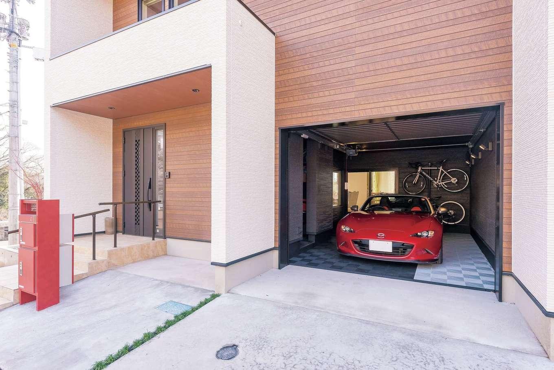 イデキョウホーム【デザイン住宅、省エネ、ガレージ】玄関は建物の角を避け、少し奥まった位置に。木の質感のある外壁がぬくもりを添える