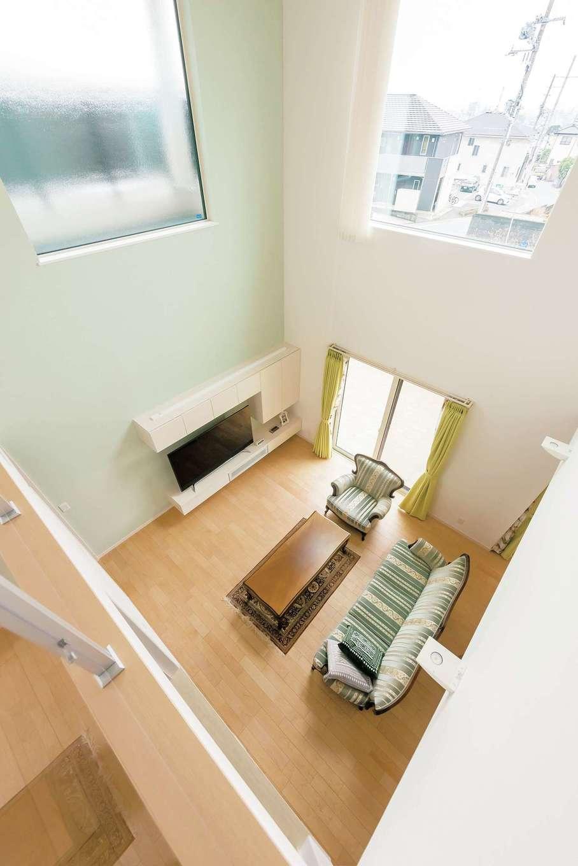 イデキョウホーム【デザイン住宅、省エネ、ガレージ】広い吹き抜けも全館空調なら寒くない。祖父から引き継いだソファの色に合わせて壁の一面をグリーンに。造作のTV台は床から浮いているように見えるデザイン