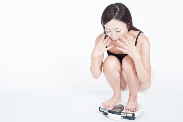 体重計に乗って驚く女性,妊娠初期,太る,