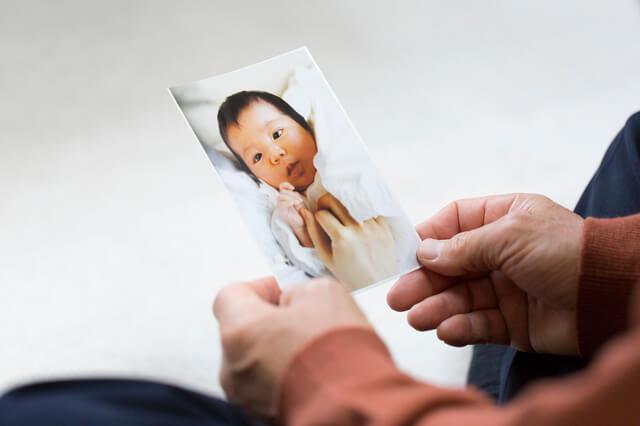 赤ちゃんの写真を眺める大人,内祝い,お菓子,