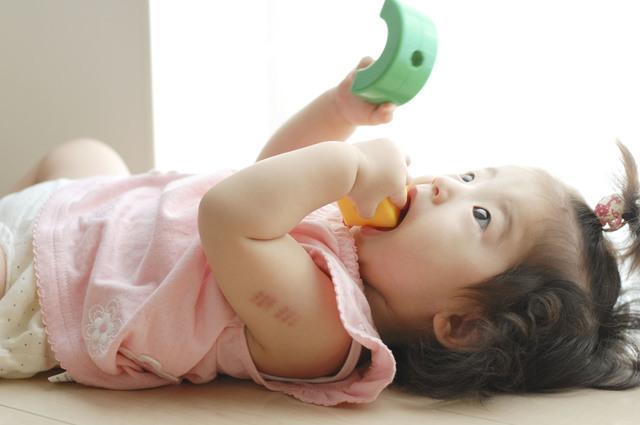 おもちゃを口に入れる赤ちゃん,赤ちゃん,おもちゃ,木