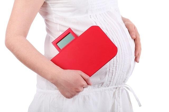 体重計を抱える妊婦,