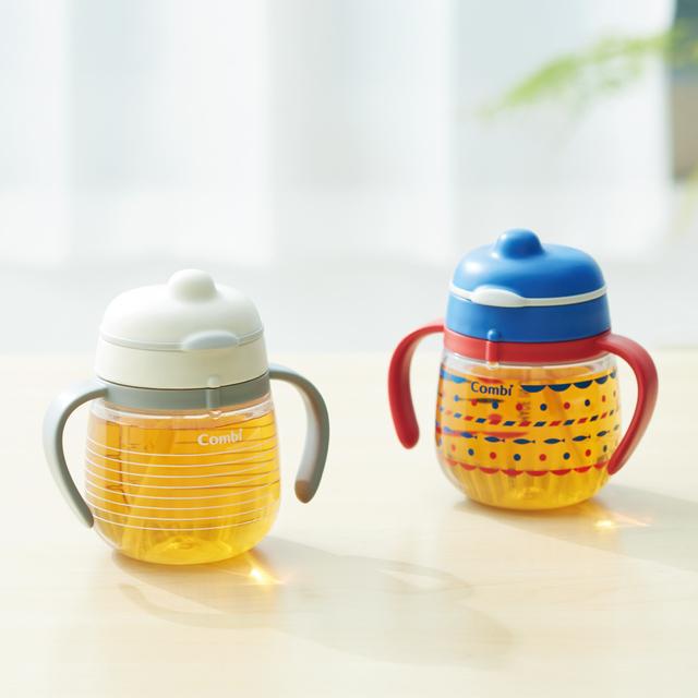 安心してマグからお茶を飲む赤ちゃん,