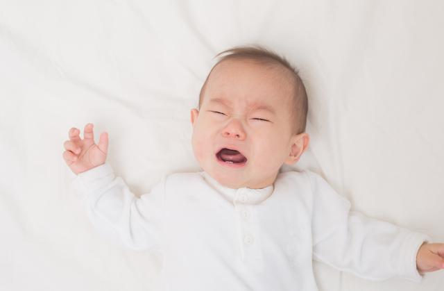 お布団で泣いている赤ちゃん,