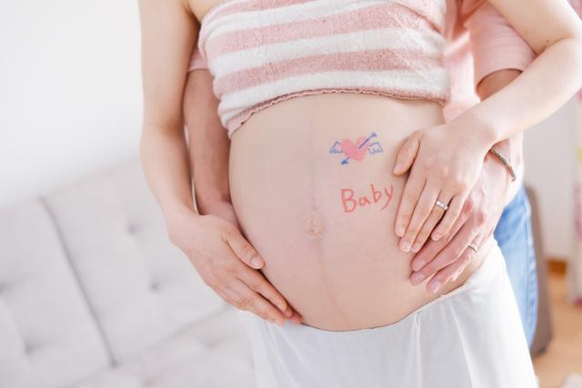 お腹に手をそえるママとパパ,妊娠22週,胎児,