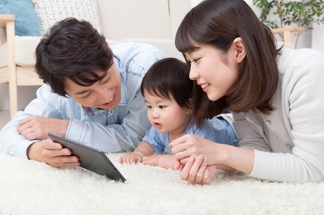 タブレットを見ている親子三人,絵本,読み聞かせ,アプリ
