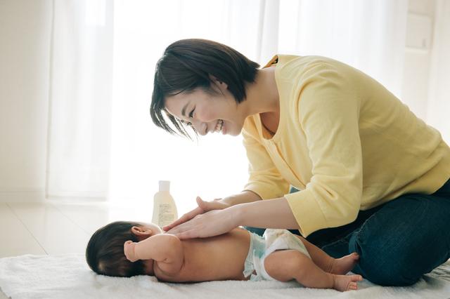 赤ちゃんにベビーローションを塗る女性,ベビーローション,