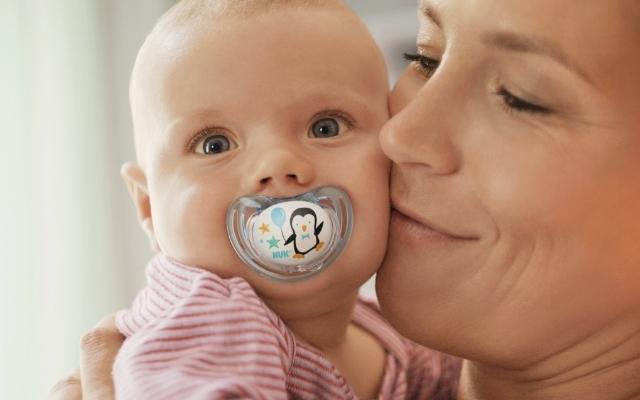 おしゃぶりをしゃぶる赤ちゃんとママ,