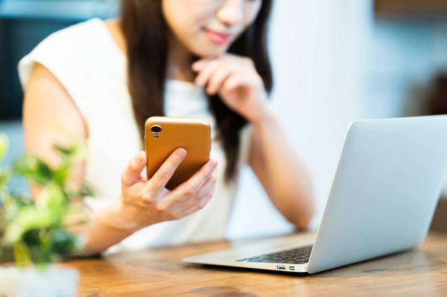 パソコンとスマホを見る女性,ベビー布団,