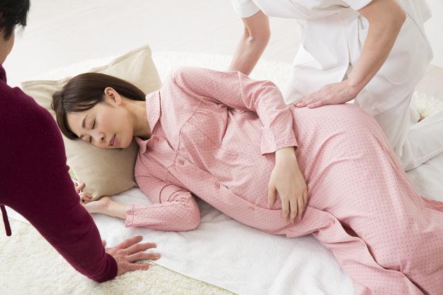 お腹の大きな妊婦と夫と助産師,出産,呼吸法,