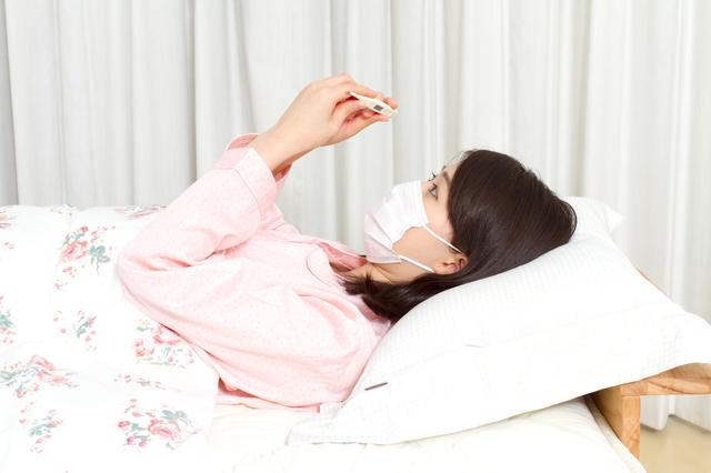 風邪で熱を測って横になる女性,妊娠,発熱,