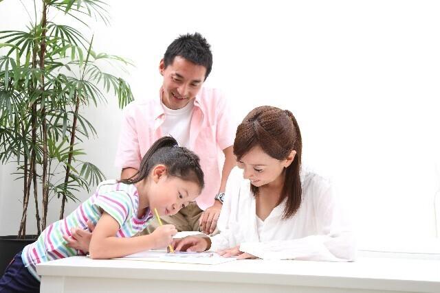 子どもの勉強を見守る両親,学資保険,