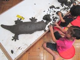 横浜美術館の子どもアトリエで粘度をこねて恐竜を形作る子どもの画像