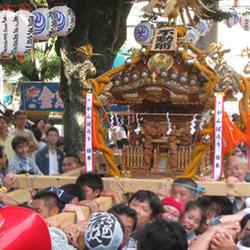 東京のお祭りと言えば御神輿を担ぐ人々の画像