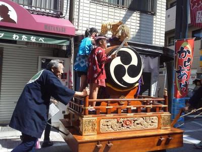 戸越銀座の商店街にある山車を押す大人と太鼓を叩く子どもたちの画像