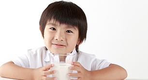 牛乳が入ったコップを持っている男の子の画像