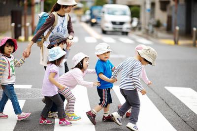 園児と先生が道路を横断している画像