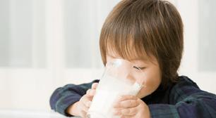 子どもがコップで牛乳を飲んでいる画像
