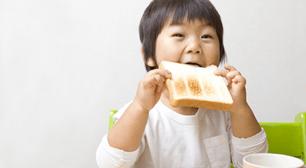 子どもが食パンを食べようとしている画像