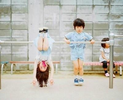 女の子と男の子が鉄棒をしている画像