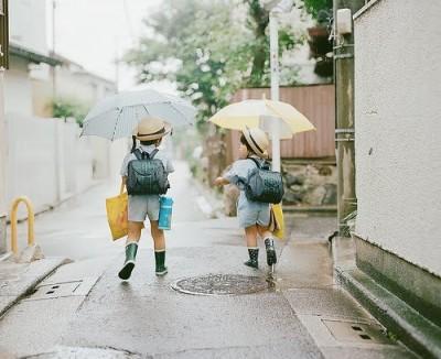 園児が傘を差して歩いている画像