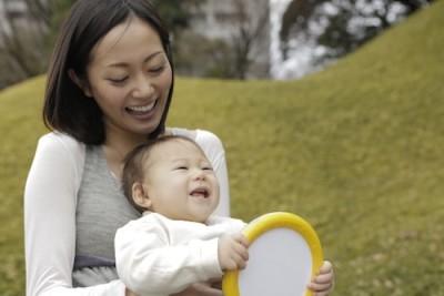 子連れで公園の遊び場でくつろぐ親子のイメージ画像