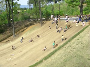 小田原わんぱく公園の傾斜を駆け上る子どもたちの画像