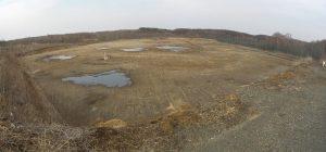 第2埋立処分地嵩上げ工事 着工前風景  工事概要:北海道千歳市美々 廃棄物の埋立を終了した埋立処分場を再稼働するため、埋立処分場の周囲に土堰堤を造成 埋立面積 19,400㎡ 埋立容量 81,600㎥ 堰堤造成盛土 34,570㎥ H=5.0m 搬入管理道路造成盛土 4,197㎥ 堰堤外周法面部張芝 8,228㎡ 堰堤内周法面部2重遮水シート設置 7,925㎡ 飛散防止ネットフェンス設置 520m H=3.0m 堰堤外周西側雨水排水用U型側溝設置 209m 雨水桝設置 7箇所 堰堤内周暗渠排水管布設 Φ150 441m 堰堤北側法面ガス抜き管設置 13箇所 竪型ガス抜き管設置 10箇所