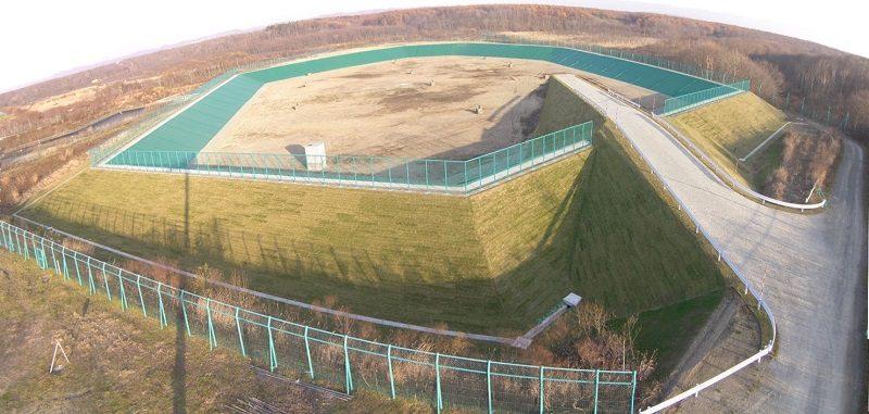 第2埋立処分地嵩上げ工事 完成風景  工事概要:北海道千歳市美々 廃棄物の埋立を終了した埋立処分場を再稼働するため、埋立処分場の周囲に土堰堤を造成 埋立面積 19,400㎡ 埋立容量 81,600㎥ 堤造成盛土 34,570㎥ H=5.0m 搬入管理道路造成盛土 4,197㎥ 堰堤外周法面部張芝 8,228㎡   堰堤内周法面部2重遮水シート設置 7,925㎡ 飛散防止ネットフェンス設置 520m H=3.0m 堰堤外周西側雨水排水用U型側溝設置 209m 雨水桝設置 7箇所 堰堤内周暗渠排水管布設 Φ150 441m 堰堤北側法面ガス抜き管設置 13箇所 竪型ガス抜き管設置 10箇所