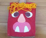 【紙袋オニ】見本作品紙袋に絵の具で着色。用意した顔のパーツを子どもたちが貼る。オニの的当てで使った新聞紙を丸めたボールを中に入れて立体感を出す。