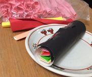 [折り紙で恵方巻き]ぷちぷちシートを寿司飯にみたて、具材は色画用紙や折り紙の他作品で作ったあとの端切れを使いました!黒折り紙を広げ、のりをつけぷちぷちシートを広げます。その上にのりをつけ、端切れ具材を細くくるくるした物を色よく並べたらあとはくるっとまき、巻き終わりをテープでぺたん!ハイ出来上がり!!手を添えてあげれば2歳児さんからも上手にまけます!節分の恵方巻き作品です!!