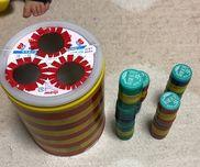 【ミルク缶 ポットン落とし】・ミルク缶・ペットボトルのキャップ(またはホースでも可)・ビニールテープ・ぺん、カッター☆切り口で子どもがケガをしないように   ビニールテープをはりましょう。☆ホースは子どもが誤飲しないように   少し長めに切りましょう。★ペットボトルのキャップだとつみきのように   重ねて遊ぶこともできます。(見本はキャップ4つをくっつけ、積み重ねています。)