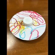 コマ1歳児クラス〈材料〉ペットボトルのフタ・厚紙・画用紙〈作り方〉画用紙になぐり描きしてもらい、綺麗に見える部分を2箇所円形に切る。厚紙を同じ大きさで、円形に切って、画用紙2枚で挟んでとめる。ペットボトルのフタ2個を合わせて止め、真ん中に差し込み、ボンドで止める。兄弟がいる子が多いために、ベイブレイドにハマっている子がいたので、指先をひねる訓練になればと思い、作った。