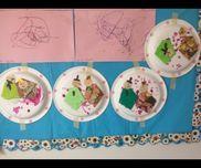 【紙皿おひなさま】1歳児保育士が折り紙、パーツを用意。子どもたちがマーカーで目と口を描きフィンガーペイントで桃を表現した紙皿におひなさまを糊で貼る。