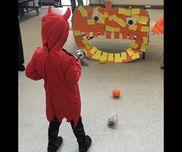ハロウィンの ボール投げゲーム(ハロウィンパーティ)ジャックオランタンの口の中に ボールを投げ入れます。かぼちゃは、子どもたちが 折り紙を貼り付け、最後に目玉を貼りました。