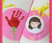 【母の日プレゼント】年少児☆手型をカーネーションに見立てて、裏に似顔絵を描いてプレゼントしました・渡す時、お母さんの首に掛けてプレゼントできるように紐は輪にして付けました。・手型に使用した絵の具はポスターカラーにのりを混ぜたものです。(乾きが早くなります)