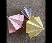 折り紙  「傘」  色画用紙に レースペーパーを貼って折る。持ち手に 針金を入れて曲げる、持ち手に輪ゴムを 巻いておくと 開いた状態で固定出来る