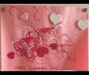 【バレンタイン製作】1歳児ハート型クッキーカッターでスタンピングハートのフォームステッカーを貼る。ステッカーを貼る際せっかくのスタンピングに重ならないように貼る場所を指で押さえてあげると良い。