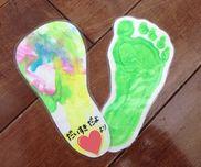 【1歳児 母の日製作 足型しおり】片面は足型裏面はフィンガーペイントパンチで穴を開けてリボンをつけて出来上がり