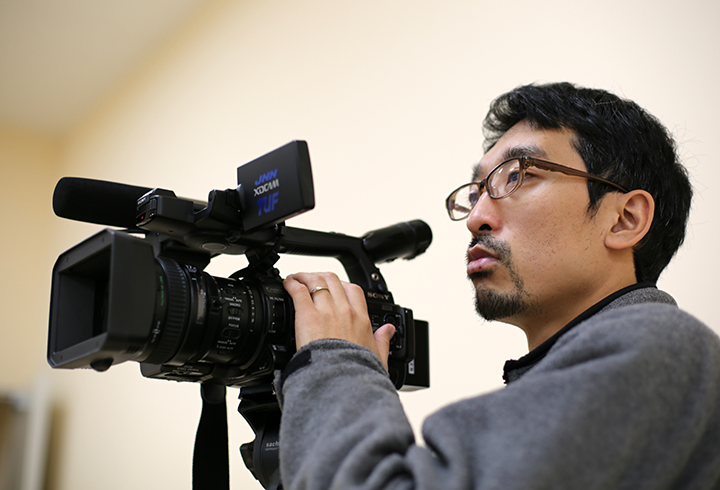 カメラを構える木田修作さん。自主避難者の住宅提供打ち切りをめぐる国の関与を明らかにするスクープ等により、日隅一雄・情報流通促進賞の特別賞を受賞した