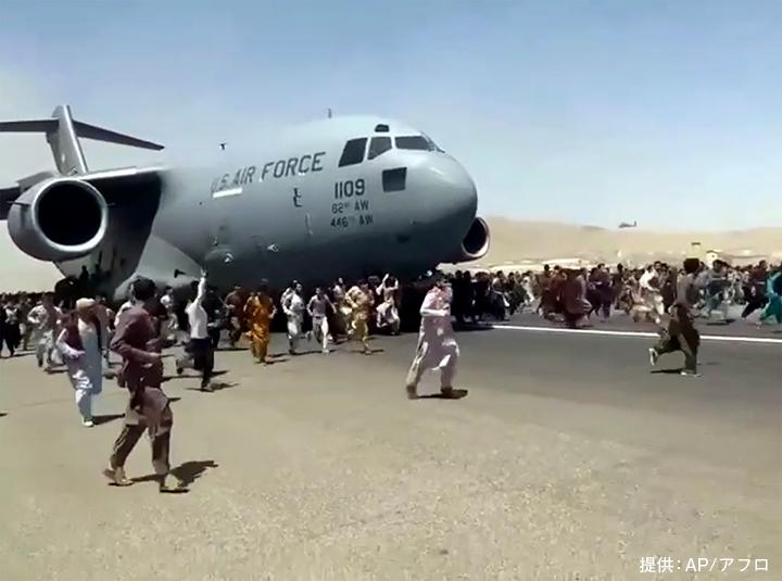タリバンが首都カブールを掌握した翌日、アフガニスタンからの出国を求めて滑走路を移動する米軍の輸送機とともに走る人々。数百人もの人々がカブール国際空港に駆けつけた(2021年8月16日、カブール国際空港)