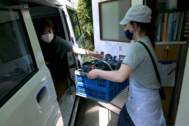 配達は車で。毎日届ける先には、回収できる弁当箱を風呂敷でまとめて届ける。撮影:篠田有史
