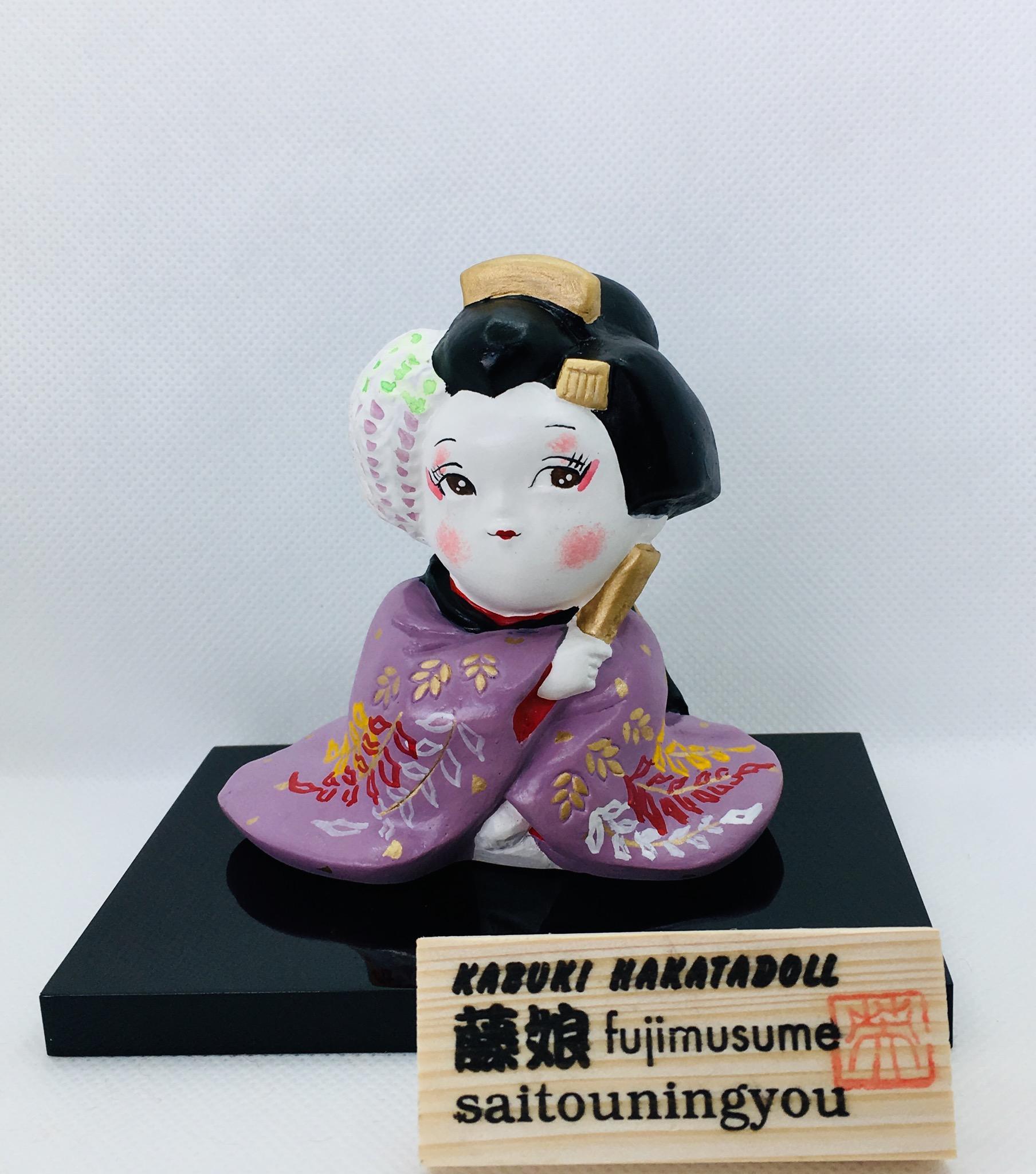 KABUKI HAKATADOLL 藤娘     高さ約9㎝  税込価格5280円   歌舞伎の舞踊の代表作ともいえる『藤娘』様々な着物に変化(へんげ)しますが、その中のひとつ、藤色の着物を纏っている姿を、わらべもの見立てで博多人形の技法を用いて作りました。   お部屋に華やかな彩りを施したい方におススメ致します。