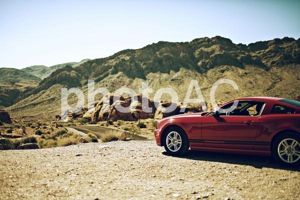 アメリカの大自然と赤い自動車の写真