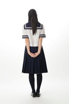 後ろで手を組む女子中学生の後ろ姿1の写真
